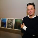 """Künstler Volker Hansen vor seinen Fotos in der """"Waschküche""""."""