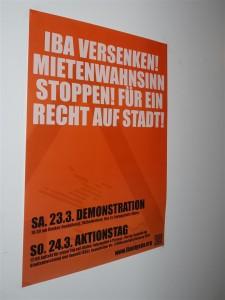 Ein Plakat weist auf die Demonstrationen am Eröffnungswochenende der IBA hin.