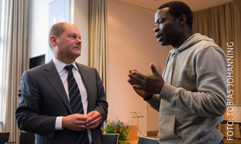 Olaf Scholz trifft auf einen Lampedusaflüchtling